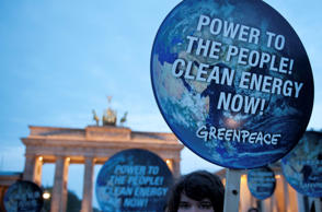 "File: Members of environmental activist group Greenpeace pose with posters which read ""Power to the people! Clean energy now"" in front of the Brandenburg Gate in Berlin April 13, 2014."