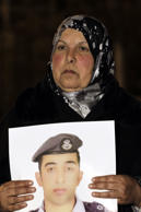 The mother of Jordanian air force pilot Maaz al-Kassasbeh, who crashed in Syria with a F-16 last month, carries a portrait of her son during a protest near the Prime Minister office in Amman late on January 27, 2015 demanding the release of Sajida al-Rishawi, an Iraqi female suicide bomber on death row in Jordan.