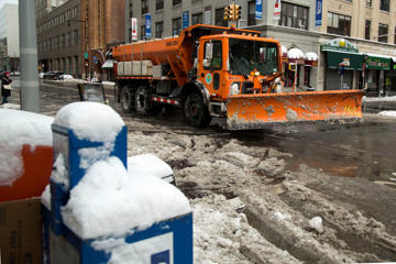 A snow plow drives down a plowed street after winter storm Juno moved through the Brooklyn borough of New York on Tuesday, Jan. 27, 2015. The storm blowing through the U.S. northeast won't drop as much snow as forecasters anticipated, sparing residents and clean-up crews the potentially life-threatening blizzard that some predicted.