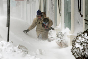 Cathleen Cahill makes her way through deep and drifting snow while walking her dog Chikita in downtown Rockport, Mass. on January 27, 2015.