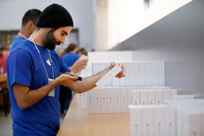 An Apple employee grabs an iPhone 6 for a customer inside the Apple Store during the launch and sale of the new iPhone 6 on Sept. 19, 2014, Palo Alto, California.