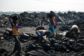 File: Day laborers fill baskets with coal at an open pit coal mine in the Bestacolla Colliery in Jharia, Jharkhand, India