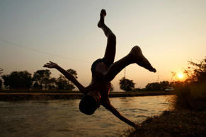 A child is silhouetted as he dives into a canal in Samraong Kandal village on January 26.