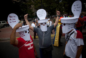 Opposition members with their faces covered with masks simulating a toilet stand on a street protesting against Venezuela's President Nicolas Maduro on January 23.