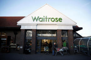 Customers push shopping carts through the entrance of a Waitrose Ltd. supermarket in the Hove district of Brighton
