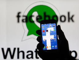 An illustration photo shows a man holding a smart phone with a Facebook logo as its screen wallpaper in front of a WhatsApp messenger logo.