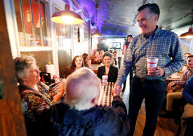 Former GOP presidential candidate Mitt Romney visits with diners at Little Dooey, a barbecue restaurant in Starkville, Miss., Wednesday, Jan. 28, 2015.