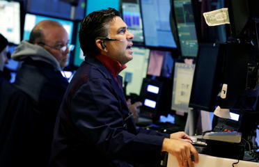 Trader Jeffrey Lucchesi, right, works in a booth on the floor of the New York Stock Exchange.