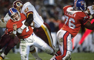John Elway #7 of the Denver Broncos gets his pass off under pressure from Monte Coleman #51 of the Washington Redskins during Super Bowl XXII on January 31, 1988 at Jack Murphy Stadium in San Diego, California. The Redskins  won the Super Bowl 42-10.