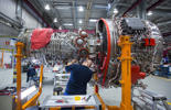 An employee works on a Rolls-Royce V2500 engine, which powers the Airbus 320 family of passenger aircraft, on the final assembly line inside Rolls-Royce Holdings Plc's aerospace unit factory in Dahlewitz, Germany, on Wednesday, Nov. 26, 2014.
