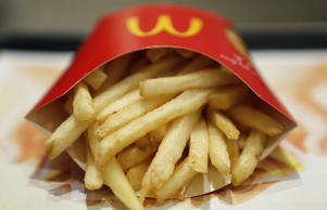 A packet of french fries sit on a tray in this arranged photograph at a McDonald's restaurant, operated by McDonald's Holdings Co. Japan Ltd., in Tokyo, Japan,