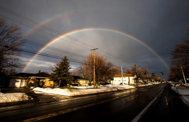 A rainbow forms over a neighborhood following a snow storm in West Seneca, New York November 24, 2014. Warming temperatures began to melt up to seven feet of snow.
