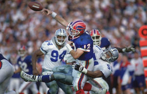 Super Bowl XXVII, Buffalo Bills QB Jim Kelly (12) in action, making pass during tackle before sustaining injury by Dallas Cowboys Ken Norton Jr, (51), Pasadena, CA 1/31/1993