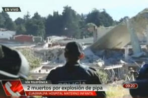 In this video frame grab image taken from Milenio TV via APTN, police look at the scene where a gas tank truck exploded outside a maternity and children's hospital in Mexico City, Thursday, Jan. 29, 2015. At least two persons reported dead and dozens injured.