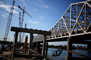 Construction crews work to erect a new highway bridge to carry I-65 traffic across the Ohio River from Louisville, Kentucky to southern Indiana as a part of the Ohio River Bridges Project in Jeffersonville, Indiana, U.S., on Aug. 13, 2014.