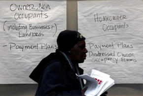 A homeowner carries paperwork to a conference room in Detroit's Cobo Center for cases being heard to avoid foreclosure from tax debts in Detroit Thursday, Jan. 29, 2015. Hundreds of Detroit homeowners at risk of losing their property are flocking to hearings that offer them a last-ditch chance to avoid foreclosure from tax debts.