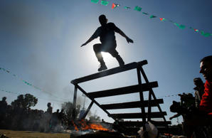 A Palestinian youth prepares to jump over a fire during a military-style graduation ceremony after being trained at one of the Hamas-run Liberation Camps, in Gaza City, January 29, 2015.