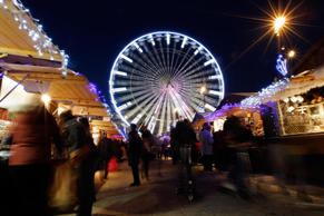 People visit a Christmas market with a Ferris Wheel.
