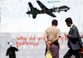 Men look at wall graffiti depicting a U.S. drone along a street in Sanaa, Yemen, on November 9, 2013.