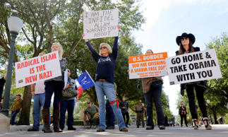 Protesters hold signs and yell to disrupt and heckle a group gathered for a Texas Muslim Capitol Day rally, Thursday, Jan. 29, 2015, in Austin, Texas. Hundreds of Muslims gathered for the rally as part of their biennial Texas Capitol lobbying day.