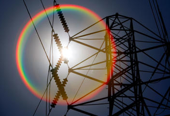 File photo of the sun shining over towers carrying electical lines in South San Francisco, Calif
