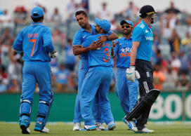India's Stuart Binny, centre, is congratulated by teammates after taking the wicket of England's Joe Root, right, during their one day international cricket match in Perth, Australia, Friday, Jan. 30, 2015.