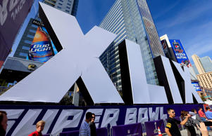 People walk past the logo for the upcoming Super Bowl XLIX between the Seattle Seahawks and New England Patriots in an NFL fan on January 28, 2015 in Phoenix, Ariz.