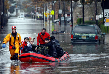 Emergency personnel and residents in the flooded streets of Little Ferry, New Jersey after Hurricane Sandy, October 30, 2012.