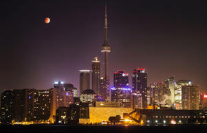 The moon turns orange during a total lunar eclipse behind the CN Tower and the skyline during moonset in Toronto October 8, 2014.