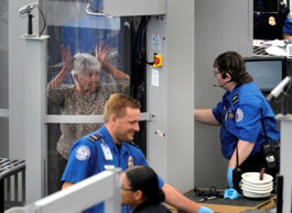 A woman gets instruction from a Transportation Security Administration agent while passing through a full body scanner at Denver International Airport in Denver, Colorado.