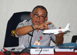 Tatang Kurniadi, chief of the National Transportation Safety Committee (NTSC), holds a model plane during a news conference in Jakarta January 29, 2015. The French first officer of an AirAsia passenger jet that crashed into the sea last month was at the controls at the time of the accident, Indonesia's National Transportation Safety Committee said on Thursday.