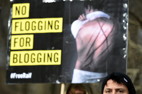 Amnesty International activists protest with a placard reading 'No flogging for blogging' against the flogging punishment of Saudi blogger Raif Badawi on January 29, 2015 in front of Saudi Arabia's embassy to Germany in Berlin. The 30-year-old Saudi has been sentenced to 1,000 lashes for insulting Islam and is serving a 10-year jail term - a case which has drawn widespread international criticism.