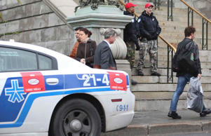 Police officers stand outside of Montreal's City Hall as an increase in security in Montreal, October 23, 2014, following Wednesday's shootings at the capital.