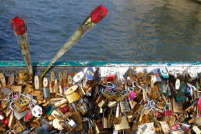 Two roses and padlocks clipped by lovers are seen on the Pont de l'Archeveche bridge, near the Notre Dame Cathedral in Paris, September 23, 2014.