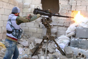 A Group 16 fighter, part of the Free Syrian Army, fires his weapon during what activists said were violent clashes with forces loyal to Syria's President Bashar al-Assad in Ashrafieh, Aleppo, January 25, 2015.