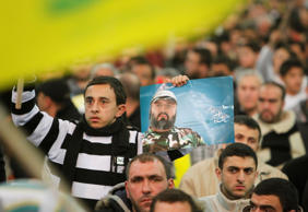 A Lebanon Hezbollah supporter waves a flag and holds a poster of assassinated Hezbollah leader Imad Mughniyah during a rally to commemorate martyrs' day in Beirut suburbs, February 16, 2012.