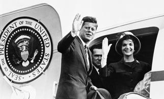 President John Kennedy and Jacqueline Kennedy wave goodbye from door of presidential plane as they prepare  to leave Vienna June 4, 1961.   They flew from Schwechat Airport in Vienna enroute to London at the end of the two-day summit meeting to Soviet Premier Nikita Khrushchev.