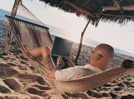 Man lying in a hammock and using a laptop computer while on a beach. Andersen Ross/Getty Images