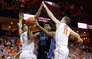 Duke Blue Devils forward Justise Winslow (12) shoots the ball as Virginia Cavaliers forward Darion Atkins (5) and Cavaliers forward Evan Nolte (11) defend in the first half at John Paul Jones Arena.