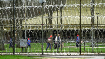 Inmates walk in the yard area at the Muskegon Correctional Facility in Muskegon, Mich.