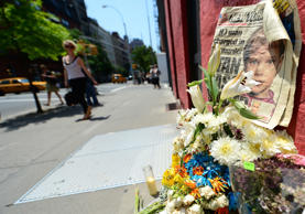 People walk past a street shrine to six-year-old Etan Patz, who disappeared 35 years ago, set in front of the building where suspect Pedro Hernandez confessed to have strangled the boy in New York on May 29, 2012.