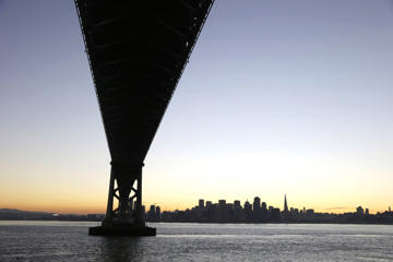 The sun sets behind the city skyline in a view from under The San Francisco-Oakland Bay Bridge on Wednesday, Jan. 7, 2015, in San Francisco.