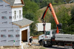 In this Wednesday, Sept. 10, 2014 photo, a crane lifts a load of drywall as construction is under way at a housing development in Zelienople, Pa. The National Association of Home Builders reports on sentiment among U.S. builders on Wednesday, Sept. 17, 2014. (AP Photo/Keith Srakocic)