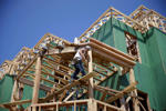 In this Wednesday, July 30, 2014 file photo, a builder works on the construction of new homes in Belmar, N.J. After a freezing winter put a cold stop to buying and selling, the U.S. economy has posted its best six months since 2003. (AP Photo/Mel Evans, File)