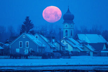 A full moon, often called the Snow Moon in the United States, sets behind a church in Regensburg, Germany, on Feb. 4, 2015.