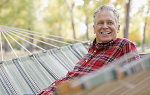Happy mature man sitting in hammock at park