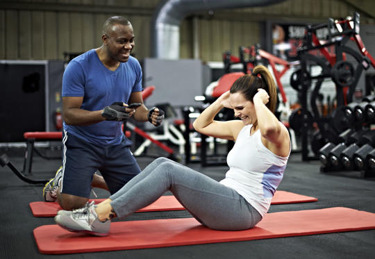 Healthy black male personal trainer encouraging healthy female doing sit ups in the gym. Using smart phone exercise app