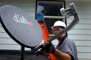 DISH Network field service specialist, Justin Preziosi, installs a satellite television system at the home of employee John Hall in Denver, CO, U.S., on Tuesday, August 6, 2013.