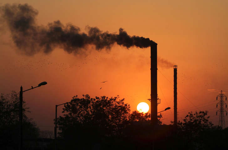 Birds fly past at sunset as smoke leaves a chimney at a factory in Ahmadabad, India, Monday, Dec. 8, 2014.