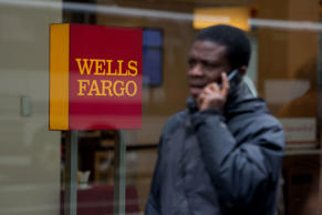 A pedestrian talks on the phone while passing in front of a Wells Fargo & Co. bank branch in New York, U.S., on Monday, April 7, 2014.